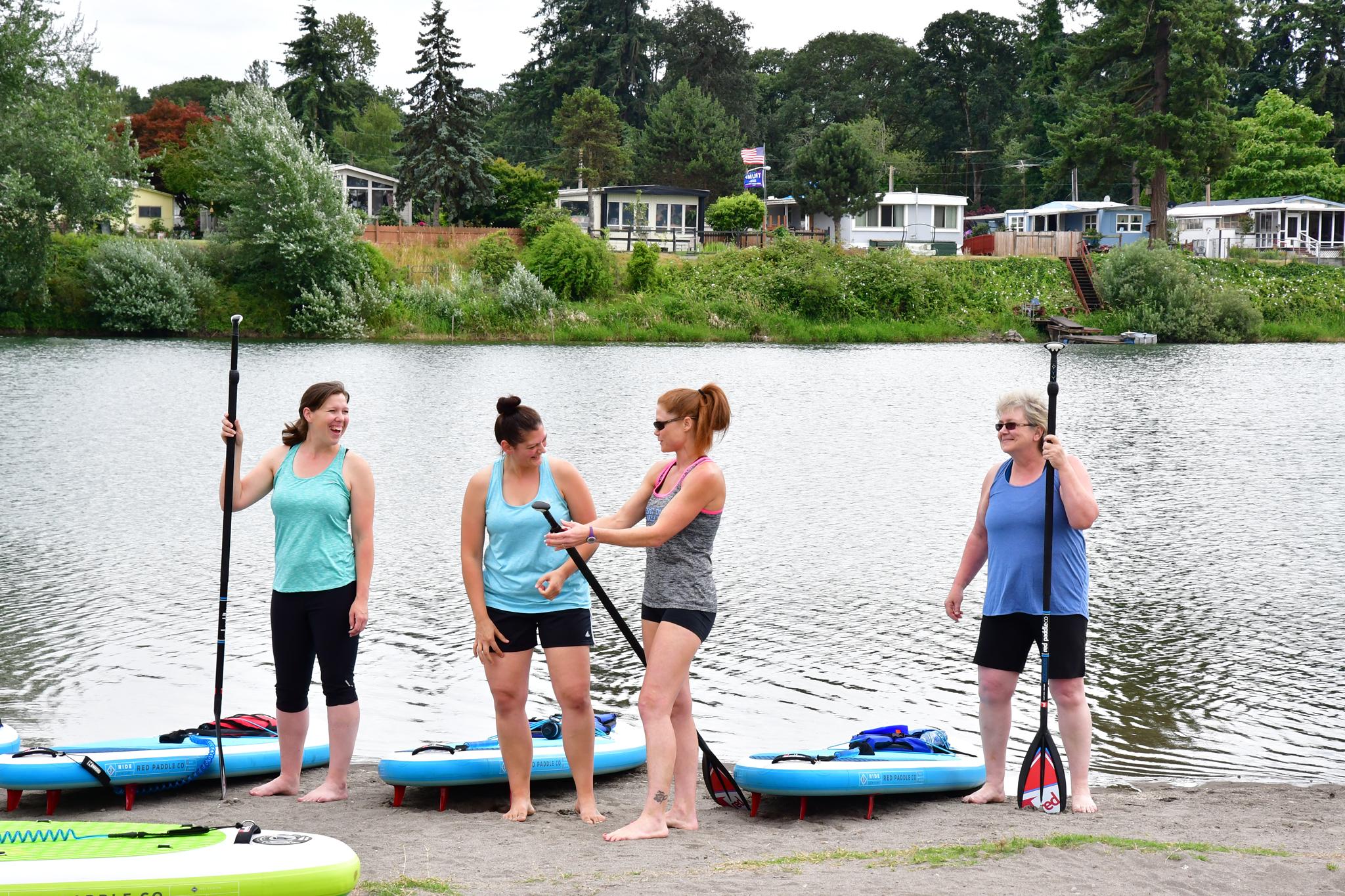 Smiling Women stand up paddleboarding in Woodland Washington