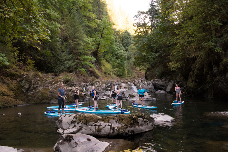 Group of women on stand up paddle boards on Lake Merwin and the Lewis River paddling