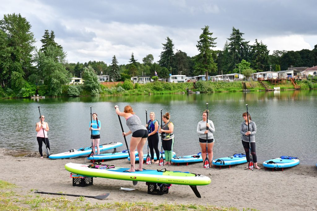 Paddle Fit Classes start on the beach, where Licensed Fitness Instructor Teaches Group Fitness to women
